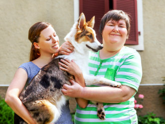two women holding dog