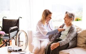 caretaker checks up elder woman with stethoscope