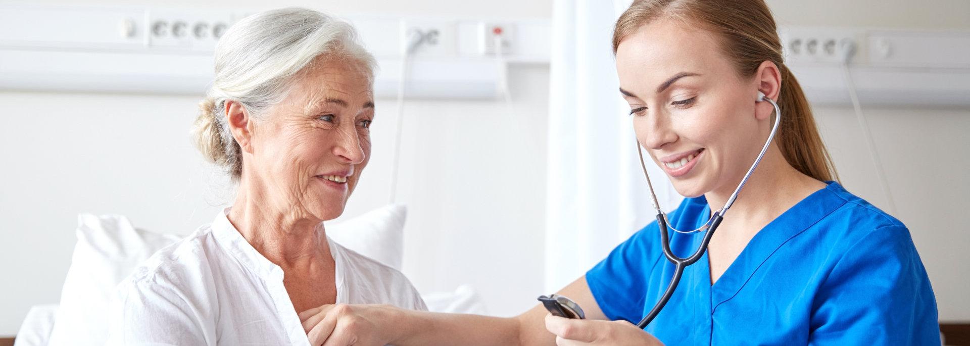 caretaker checks elder woman's heartbeat