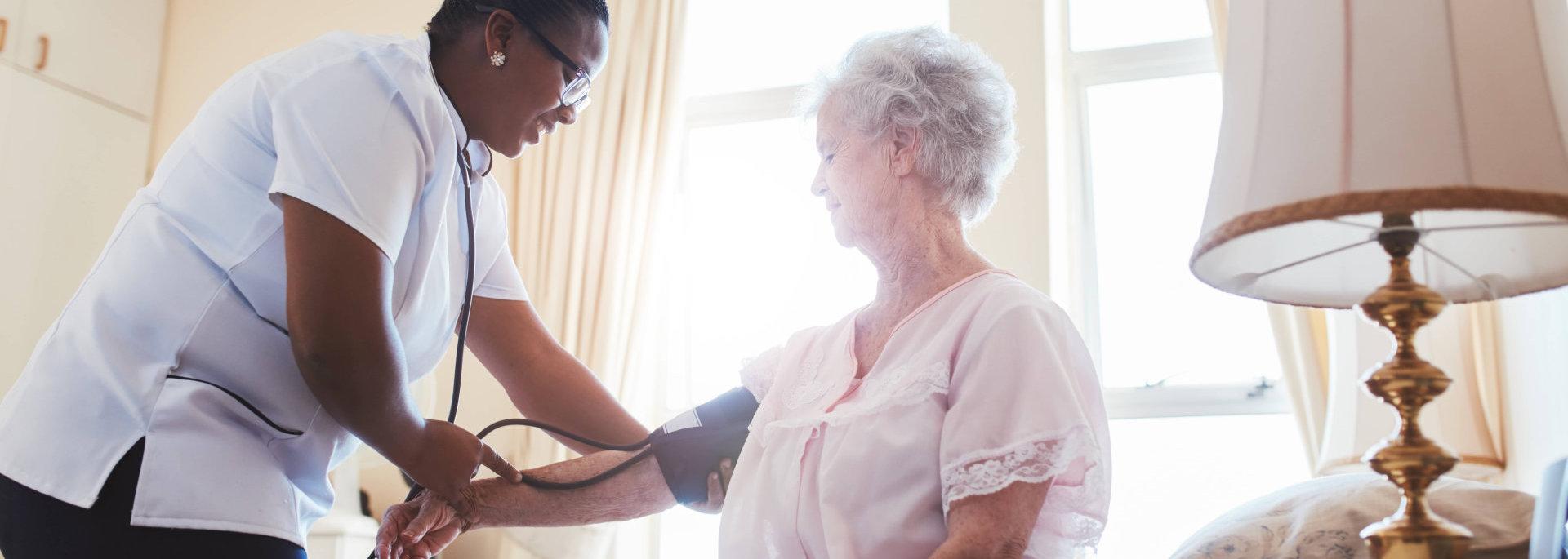 caretaker doing bp test on elder woman