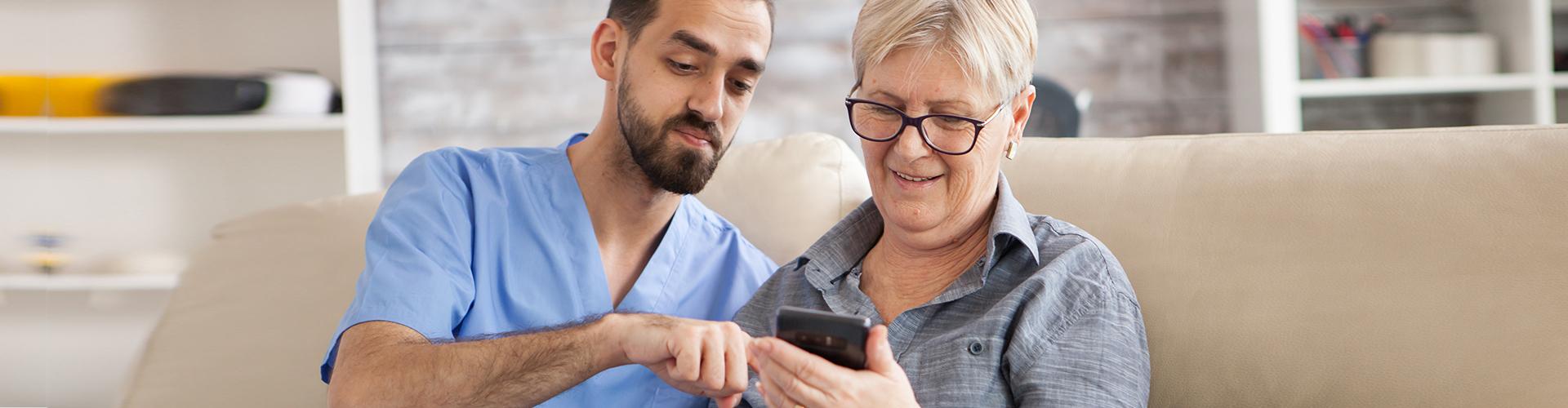 caretaker helping elder lady with phone