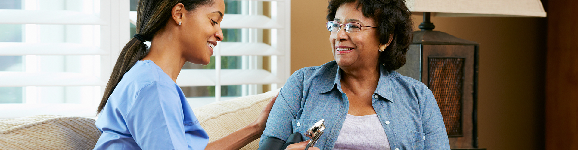 caretaker checks elder woman using stethoscope